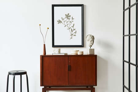 Modern retro concept of living room interior with design teak commode, black mock up poster frame, dried flower, decoration, white wall and personal accessories. Template.