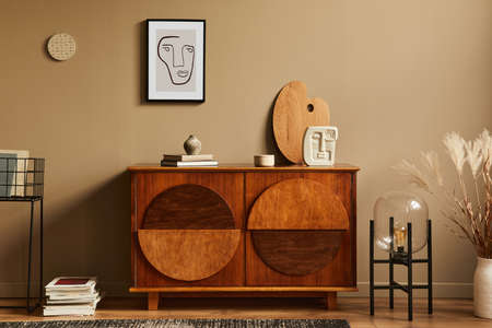 Stylish interior with design wooden commode, lamp, dried flowers in vase, unique decoration, carpet, mock up poster frame and elegant personal accessories. Modern living room in classic house. 版權商用圖片
