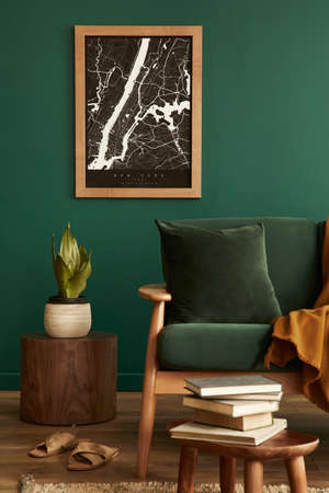 Stylish living room in house with modern retro interior design, velvet sofa, carpet, stool, brown wooden furniture, plants, poster mock up map, book, lamp and perosnal accessories in home decor.
