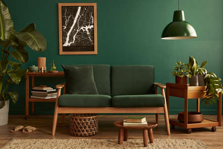 Stylish living room in house with modern retro interior design, velvet sofa, carpet on floor, brown wooden furniture, plants, poster mock up map, book, lamp and perosnal accessories in home decor. 版權商用圖片