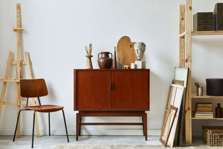 Stylish composition of artist workspace with design retro teak commode, chair, bookcase, poster frames, easel, decoration and elegant personal accessories. Template.