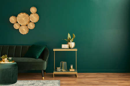 Elegant living room interior with modern design, green velvet sofa, furniture, gold decoration, plant, carpet, copy space, pillow and stylish personal accessories. Template.