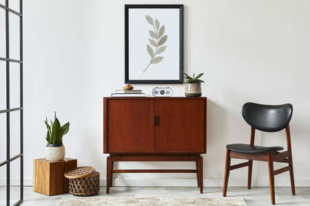 Stylish interior design of living room with wooden retro commode, chair, plant, rattan decoration, cube and elegant personal accessories. Mock up poster frame on the white wall. Template.