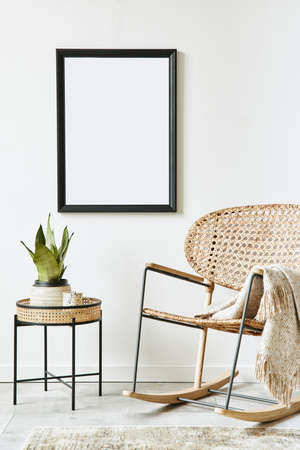 Retro modern compositon of living room interior with design rattan armchair, black mock up poster frame, coffee table, plant, decoration, white wall and personal accessories. Template. 版權商用圖片