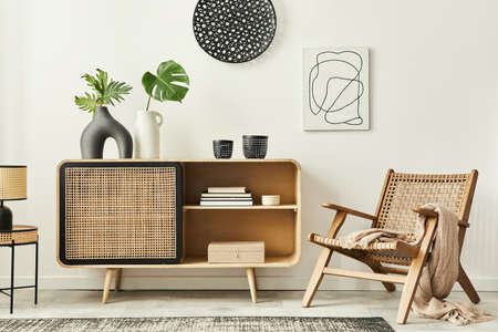 Stylish scandinavian living room interior of modern apartment with wooden commode, design armchair, carpet, leaf in vase, table lamp and personal accessories in unique home decor. Template.