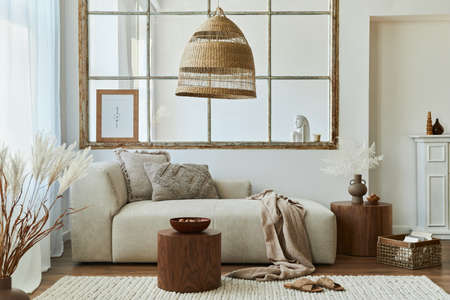 Stylish interior of living room with design modular sofa, furniture, wooden coffee table, rattan decoration, mock up picture frame, pillow, dried flowers and elegant accessories in modern home decor. Banque d'images