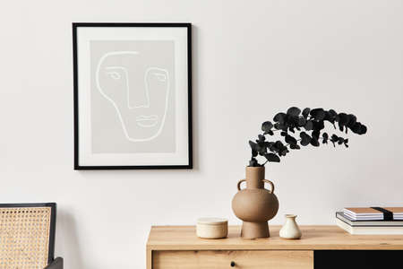 Stylish interior of living room with mock up poster frame, wooden commode, book, eucalyptus leaf in ceramic vase and elegant personal accessories. Minimalist concept of home decor. Template. Reklamní fotografie