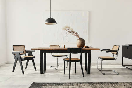 Minimalist composition of dining room interior with wooden table, design chairs, dried flowers in a vase, black pendant lamp, art paintings on the wall and elegant personal accessories. Template. Imagens