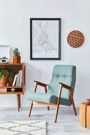 Retro composition of living room interior with mock up poster map, wooden shelf, book, stool, armchair, plant, cacti, vinyl recorder and personal accessories in stylish home decor. Archivio Fotografico