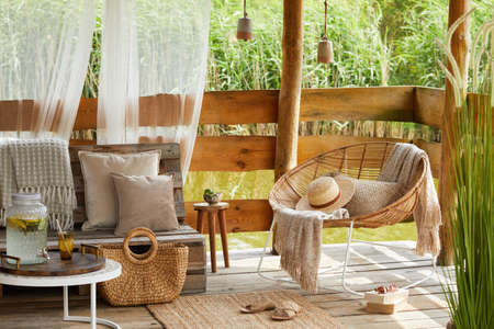 Interior design of summer gazebo by the lake with stylish rattan armchair, coffee table, sofa, pillows, plaid and elegant accessories in modern decor. Summer vibes.