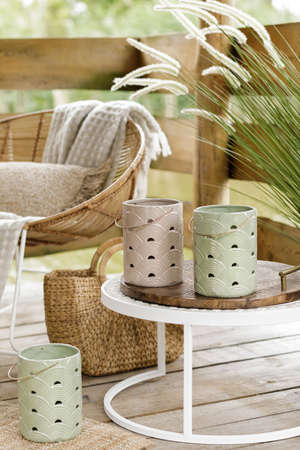 Stylish interior design of summer wooden gazebo by the lake with neutral furnitures, lanterns, bag and elegant accessories. Summer mood. Outdoor space. Template.