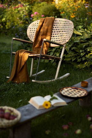 Stylish composition of countryside garden with design rattan armchair, wooden bench, plaid, food, drinks and elegant accessories. A lot of colorful flowers. Summer mood.