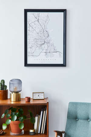 Retro composition of living room interior with mock up poster map, wooden shelf, book, armchair, plant, cacti, vinyl recorder and personal accessories in stylish home decor.