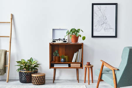 Modern retro composition of living room interior with design wooden cabinet, stylish armchair, mock up poster map, plants, vinyl recorder, books and personal accessories in home decor. Template.