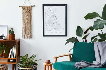 Stylish interior of living room with design wooden shelf, velvet sofa, a lot of plants, mock up poster map, vinyl recorder, book, macrame and personal accessories in vintage home decor. Template. Stock fotó
