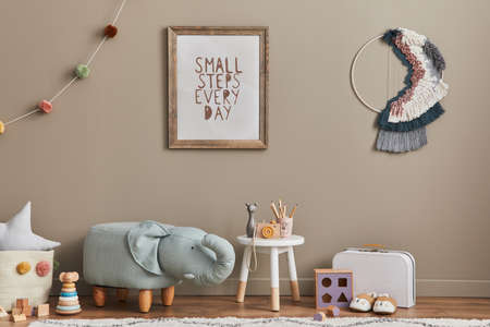 Stylish scandinavian kid room interior with toys, elephant pouf, plush animal toys, furniture, decoration and child accessories. Brown wooden mock up poster frames on the wall. Template 版權商用圖片