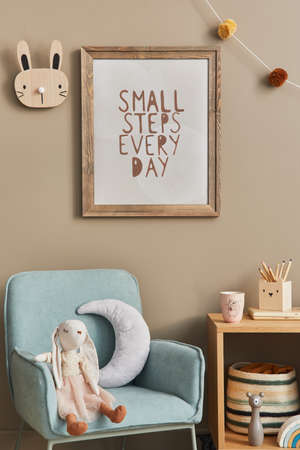 Cozy interior of child room with mint armchair, brown mock up poster frame, toys, teddy bear, dolls, plush animal, decoration. Beige wall. Warm kid space. Template.