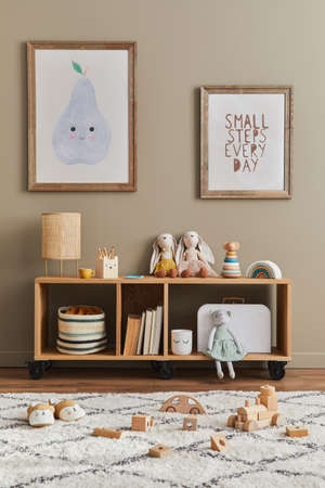 Stylish scandinavian kid room interior with toys, teddy bear, plush animal toys, furniture, decoration and child accessories. Brown wooden mock up poster frames on the wall. Template