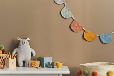 Interior design of stylish kid room space with white shelf, wooden toys, child accessories, cozy decoration and hanging cotton flags on the beige wall. Template.