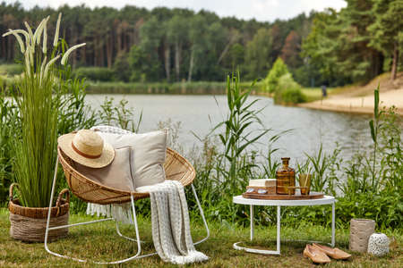 Stylish composition of outdoor garden on the lake with design rattan armchair, coffee table, plaid, pillows, drinks and elegant accessories. Summer vibes. Stock fotó