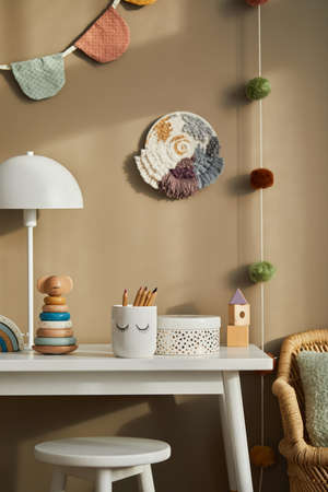 Interior design of stylish kid room space with white shelf, wooden toys, dolls, child accessories, white lamp, cozy decoration and hanging cotton flags on the beige wall. Template. Stock fotó