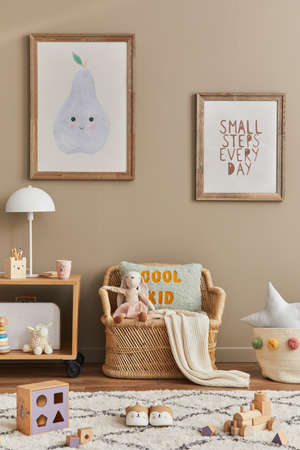 Stylish scandinavian kid room interior with toys, teddy bear, plush animal toys, rattan sofa, furniture, decoration and child accessories. Brown wooden mock up poster frames on the wall. Template Stock fotó