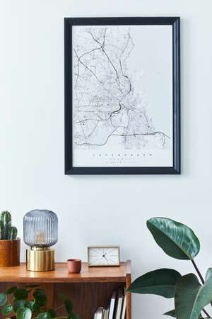 Stylish scandinavian living room interior with retro commode, black mock up poster frame, clock, plan, decoration, book and personal accessoreis in home decor. Template.
