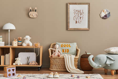 Stylish scandinavian kid room interior with toys, teddy bear, plush animal toys, rattan sofa, furniture, decoration and child accessories. Brown wooden mock up poster frames on the wall. Template 版權商用圖片