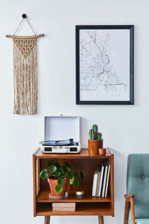 Retro composition of living room interior with mock up poster map, wooden shelf, book, macrame, armchair, plant, cacti, vinyl recorder and personal accessories in stylish home decor.