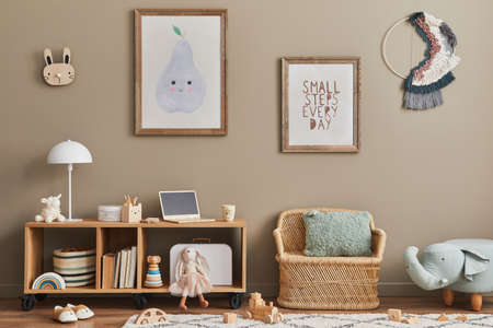Cozy interior of child room with mint armchair, brown mock up poster frame, toys, teddy bear, plush animal, decoration and hanging cotton colorful balls. Beige wall. Warm kid space. Template.