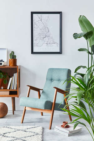 Stylish interior of living room with design wooden shelf, retro armchair, plants, mock up poster map, decoration, book, cacti and personal accessories in retro home decor. Template.