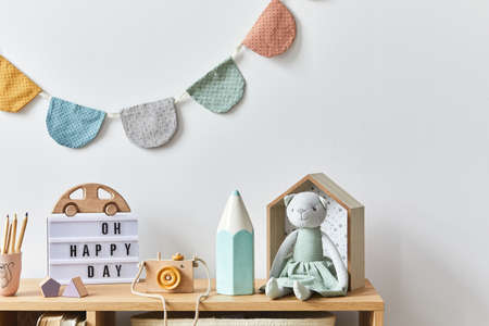 Stylish scandinavian newborn baby room with toys, plush animal, photo camera, dolls and child accessories. Cozy decoration and hanging cotton balls on the white wall. Copy space.