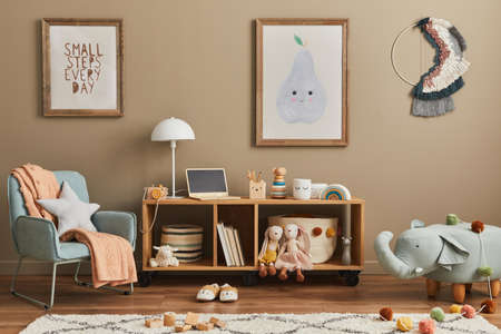 Stylish scandinavian kid room interior with toys, teddy bear, plush animal toys, mint armchair, furniture, decoration and child accessories. Brown wooden mock up poster frames on the wall. Template