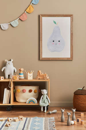 Stylish scandinavian newborn baby room with brown wooden mock up poster frame, toys, plush animal and child accessories. Cozy decoration and hanging cotton flags on the beige wall. Template.