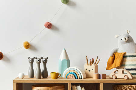 Stylish scandinavian newborn baby room with toys, plush animal, photo camera and child accessories. Cozy decoration and hanging cotton balls on the white wall. Copy space.