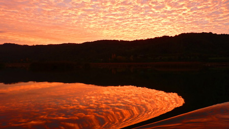 Sky and water seem to burn in this incredible red sunset shot.The boat ripple makes it all peculiar.The picture was taken in Valdivia, Chile
