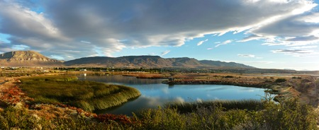 calafate: Nimez Lagoon at the golden hourThe idyllic Nimez Lagoon at the golden hour.Surrounded by reeds and topped by a cloudy sky.Remarkable reflection and precious light for this wide panorama.The picture was taken in El Calafate, Argentina