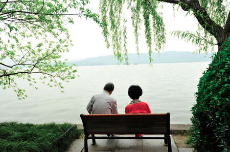 Old couple relax near big lake, China photo