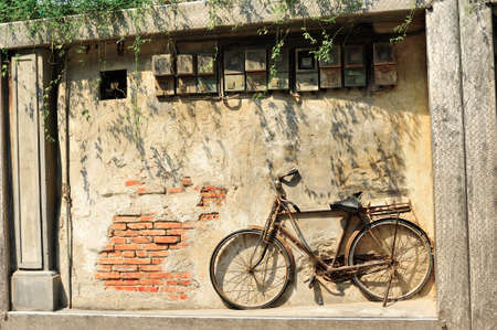 Old bicycle on vintage house, China photo