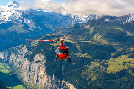 helicopter: Red helicopter at around Jungfrau mountain swiss alps