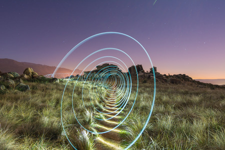 light painting: Abstract spiral light painting in a field Stock Photo