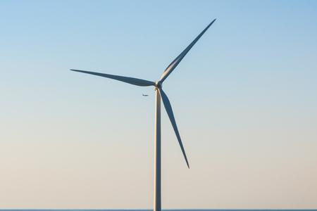 planos electricos: generador de viento en el cielo azul con un avión en el fondo Foto de archivo