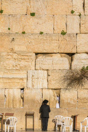 ancient tradition: Orthodox Jewish man prays in the Wailing Wall of Jerusalem, Israel Stock Photo