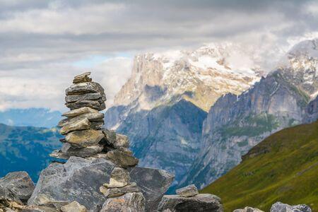 Kleine Steinhügel mit den schneebedeckten alpinen Bergen im Hintergrund Standard-Bild