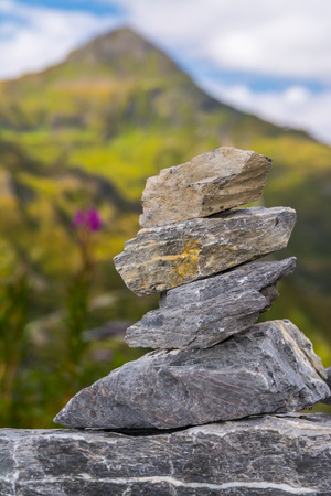 cairn: Small cairn with green mountain at background