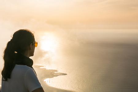 mujer mirando el horizonte: Joven disfrutando de la hermosa puesta de sol desde el punto de vista