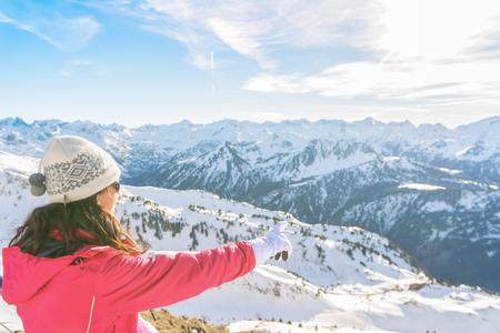 Sciatore della giovane donna che gode delle viste nevose delle montagne da un punto di vista