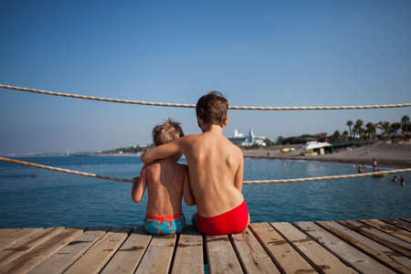 Two brothers sit on the pier and look at the sea