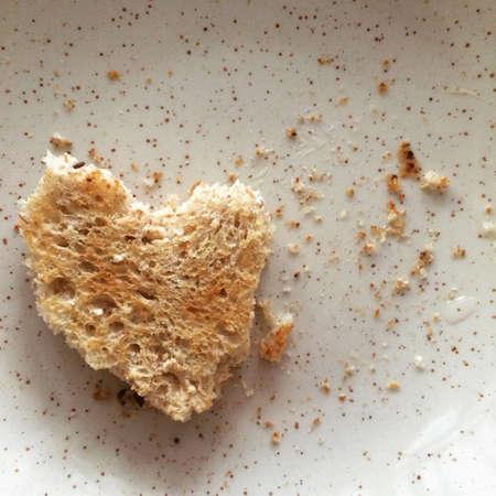 heart burn: A heart shape toast on a tiny brown dot white plate