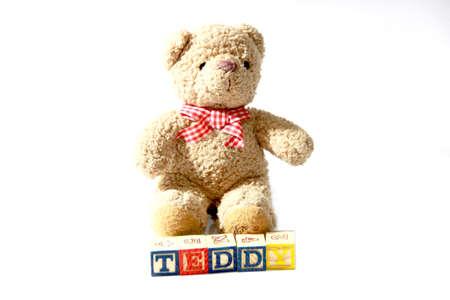 and spelling: Teddy Bear Sitting with alphabet blocks spelling TEDDY Stock Photo